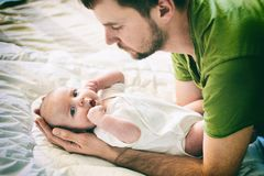Father and child on a white bed. Father and baby boy in diaper playing in sunny bedroom. Father makes gymnastics for his newborn b. Aby. Parent and little kid Stock Photography