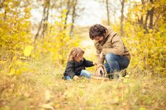 Father and child in the wild forest. Father and child searching mushrooms in the wild forest, dad and kid friendship. Fall day. Little girl exploring nature royalty free stock image