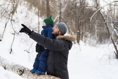 Father and child in a winter forest Stock Photo