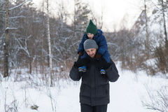 Father and child in a winter forest Royalty Free Stock Photo