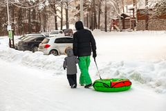 Father with a child in winter suits go down the hill with a bun for riding in the snow in the hands to the parking lot to his car royalty free stock photography
