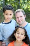 Father and Children. A father with his children standing outside Royalty Free Stock Image