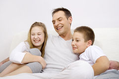 Father with children. Happy family siting on couch Royalty Free Stock Image