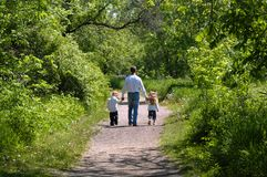FATHER AND CHILDREN. A father walks down a path in a wooded area holding hands with his son and daughter Stock Photo