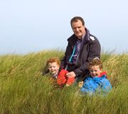 Father with Children. Outdoor portrait of a father and his two sons, sitting in high grass Royalty Free Stock Images