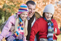 Father and children on autumn walk. Sitting on fence Stock Photography