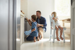 Father And Children Baking Homemade Pizza In Oven Royalty Free Stock Images