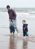 Father with children on the beach Royalty Free Stock Image