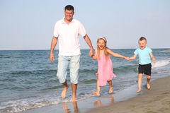 Father with children at the beach. Father is running with his children at the beach stock photography