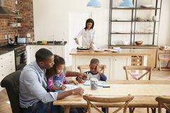 Father And Children Drawing At Table As Mother Prepares Meal royalty free stock image