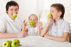 Father and children eating apples Royalty Free Stock Photography