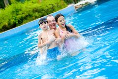 Father with  children enjoying the swimming pool Stock Photos