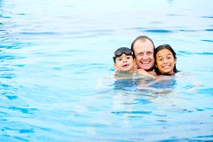 Father with children enjoying the swimming pool Royalty Free Stock Images
