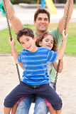 Father and children enjoying swing ride Stock Images