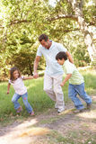 Father And Children Enjoying Walk In Park Royalty Free Stock Photos