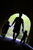 Father and Children Exploring Dark Tunnel Stock Images
