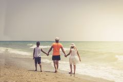 Father with children having fun on the beach at the day time. Father with children having fun on the beach at the day time stock image