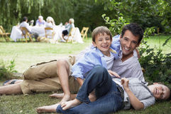 Father And Children Having Fun In Garden. Portrait of happy father and children having fun in grass with family in background Royalty Free Stock Photos
