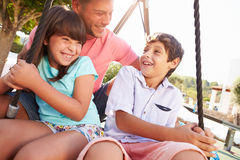 Father And Children Having Fun On Swing In Playground Stock Images