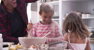 Father With Children Having Messy Fun Baking In Kitchen