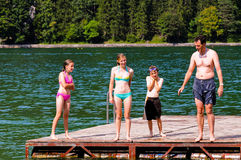 Father and children at the lake. Portrait of father and children swimming in the lake royalty free stock photos