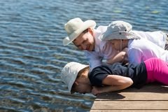 Father with children lie and look at a beautiful lake and fish in the water. Father with children  lie and look at a beautiful lake and fish in the water Stock Image