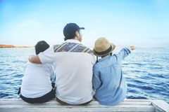 Father with children looking at the blue ocean Stock Images