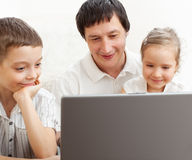 Father with children looking laptop Royalty Free Stock Images