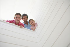 Father With Children Looking Over White Wall Royalty Free Stock Images