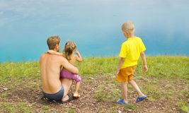Father and children looking at the water Stock Image