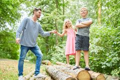 Father and children on a nature trip. Climb on tree trunks royalty free stock image
