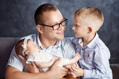 Father with children newborn baby girl and older brother. Happy stock photo