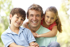 Father With Children In Park. Smiling To Camera royalty free stock photo