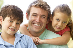 Father With Children In Park. Smiling To Camera royalty free stock image