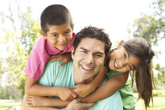 Father With Children In Park. Having piggyback, smiling to camera stock photography