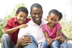 Father With Children In Park. Smiling royalty free stock image