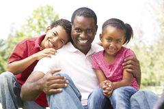 Father With Children In Park. Smiling royalty free stock photography