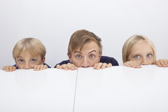 Father and children peeking over table Royalty Free Stock Photography