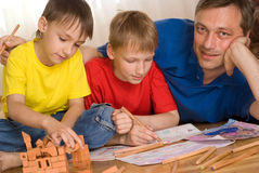 Father with children playing. On the floor Royalty Free Stock Image