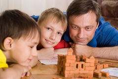 Father with children playing. On the floor Royalty Free Stock Photos