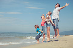 Father and children playing on the beach at the day time. Royalty Free Stock Image