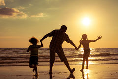 Father and children playing on the beach at the sunset time. Stock Image