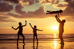 Father and children playing on the beach at the sunset time. Royalty Free Stock Images