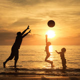 Father and children playing on the beach at the sunset time. Stock Images