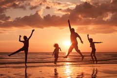 Father and children playing on the beach at the sunset time. Stock Photo