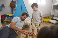 Father And Children Playing With Building Blocks In Bedroom Royalty Free Stock Images