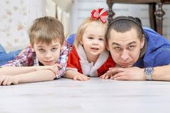 Father with children playing in Christmas living room. Portrait of friendly family looking at camera on Christmas evening. Winter holiday Xmas and New Year Royalty Free Stock Photography