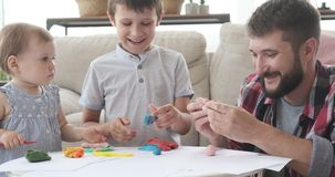 Father and children playing with plasticine. Happy father and children playing with plasticine at home stock video footage