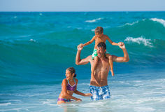 Father and children playing in the sea Stock Images