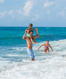 Father and children playing in the sea Stock Image